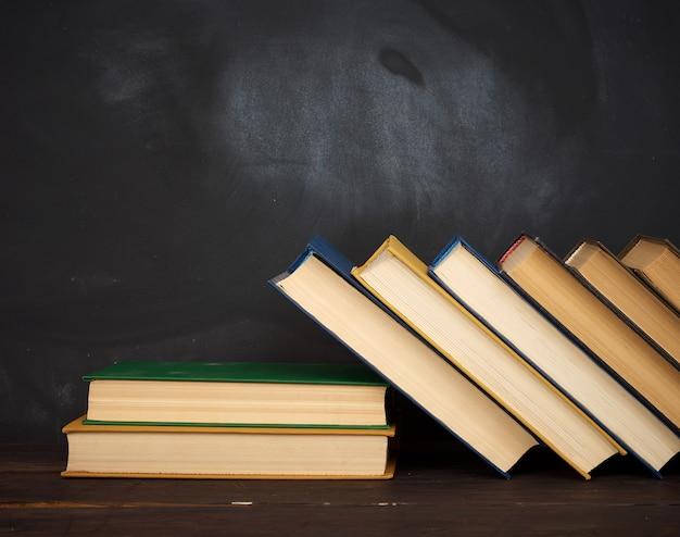Vari libri con copertina rigida sullo sfondo di un bordo di gesso nero vuoto