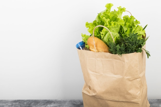 Vario alimento sano in sacco di carta su spazio grigio. copia spazio. spazio alimentare