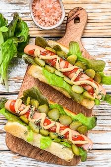 Vari hot dog con verdure, lattuga e condimenti. fondo in legno bianco. vista dall'alto.