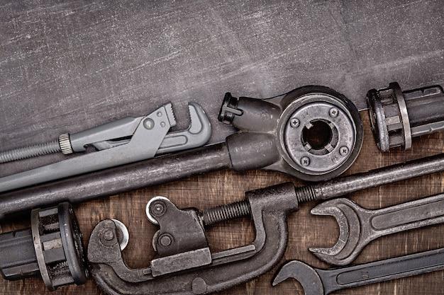 Vari attrezzi idraulici domestici sulla superficie di legno marrone e metallica