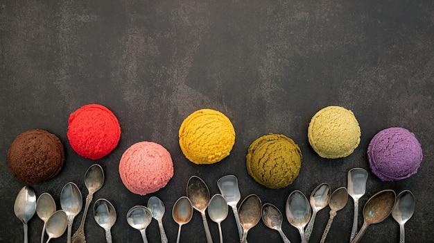Vari gusti di gelato al mirtillo, al pistacchio, alla mandorla, all'arancia, al tè verde e al cioccolato su sfondo di pietra scura. concetto di menu estivo e dolce.