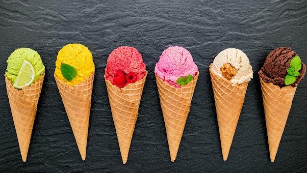 Vari gusti di gelato in coni allestiti su sfondo di pietra scura.