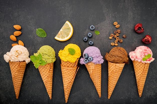 Vari gusti di gelato in configurazione coni su sfondo di pietra scura.