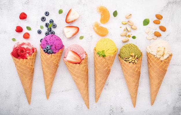 Vari gusti di gelato in coni montati su pietra bianca.