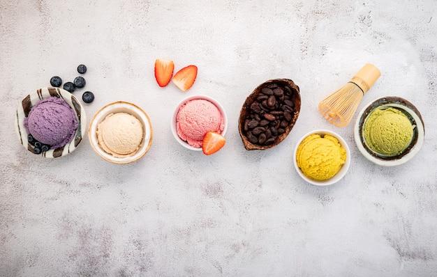 Vari gusti di gelato nella configurazione della ciotola su priorità bassa di pietra bianca