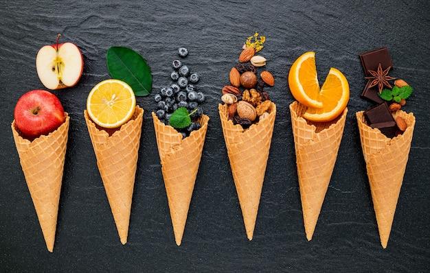 Vari ingredienti per il gusto del gelato in coni allestiti su sfondo di pietra scura. concetto di menu estivo e dolce.