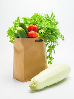 Vari ingredienti per insalata di verdure verdure verdi appena raccolte in un sacchetto di carta artigianale su una superficie bianca