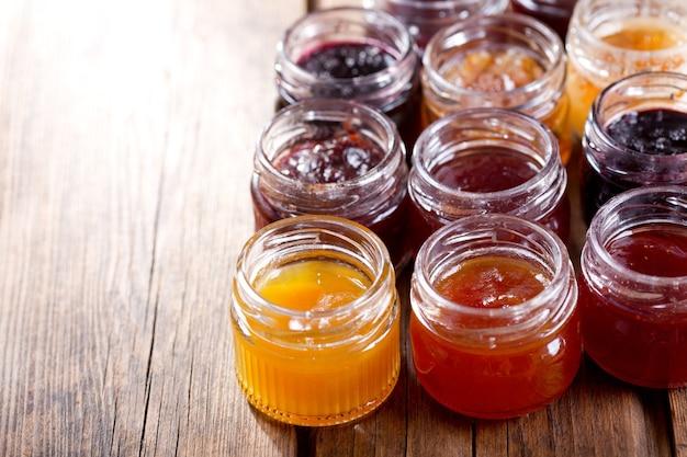 Vari vasetti di marmellata di frutta sul tavolo di legno