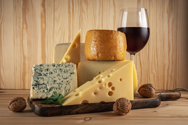 Vari tipi di formaggio con un bicchiere di vino sulla tavola di legno.
