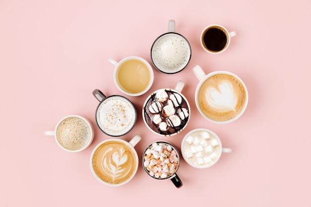 Vari tipi di caffè in tazze di diverse dimensioni su sfondo rosa pallido