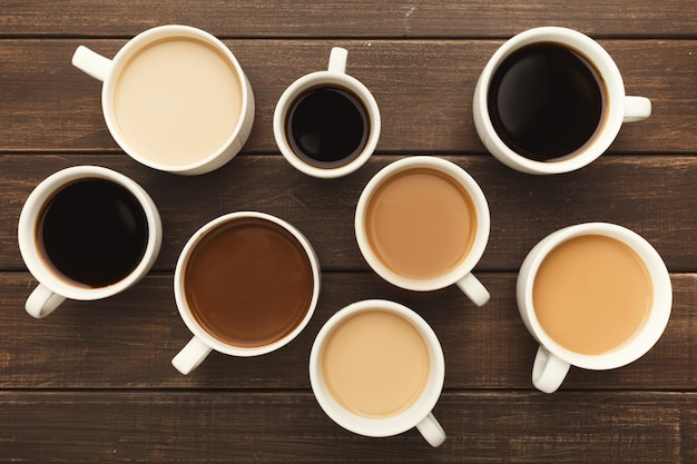 Vari tipi di caffè in tazze di diverse dimensioni su tavola in legno rustico, vista dall'alto