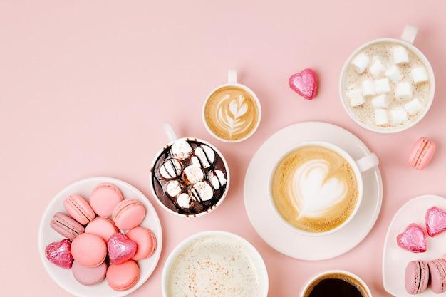 Vari tipi di caffè in tazze di diverse dimensioni con caramelle e amaretti su sfondo rosa pallido