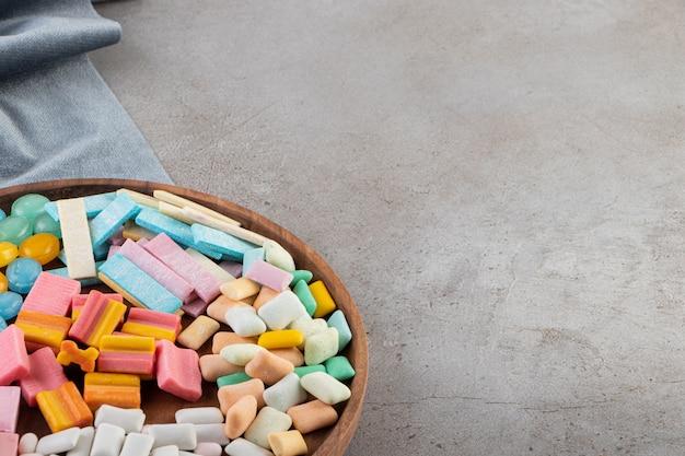 Vari tipi di gomme sul vassoio in legno su sfondo grigio.