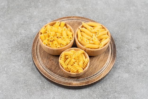 Vari tipi di pasta in ciotole su legno.