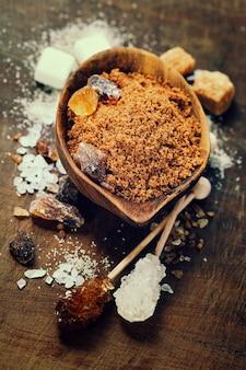 Vari tipi di zucchero in ciotole di legno