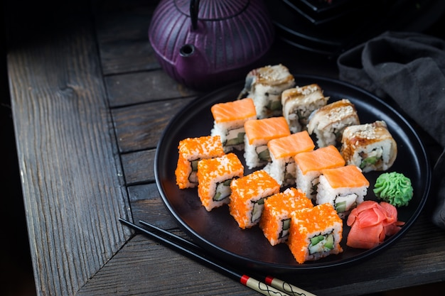 Vari tipi di rotoli di sushi serviti sulla banda nera nel buio