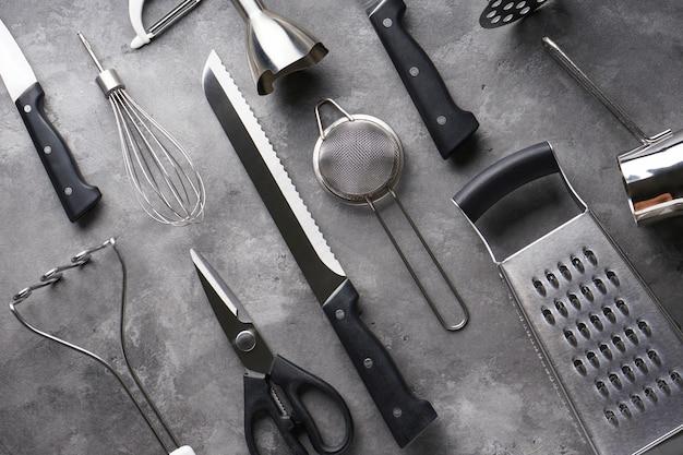 Vari utensili della cucina sulla tavola grigia, primo piano.