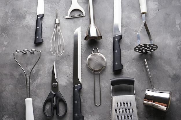 Vari utensili da cucina sul tavolo grigio, piatto laici.