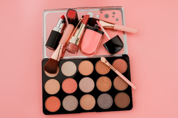 Vari prodotti per il trucco su sfondo rosa con copyspace.