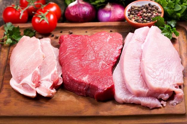 Varie carni su una tavola di legno con ingredienti per cucinare