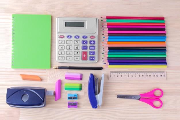 Vari articoli di cancelleria multicolori e accessori per la scuola su un tavolo di legno naturale. vista dall'alto