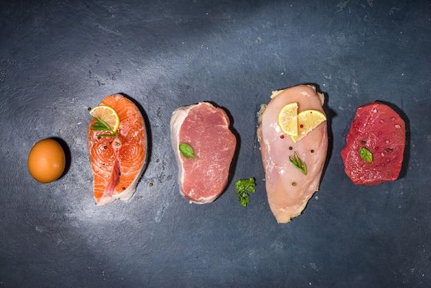 Vari alimenti naturali, alte fonti di proteine animali - carne di maiale, bistecche di carne di manzo, filetto di petto di pollo, uova, salmone su sfondo bianco tavolo vista dall'alto spazio copia