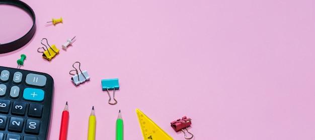 Varie forniture per ufficio su uno sfondo rosa torna a scuola concetto calcolatrice e lente d'ingrandimento con pe...