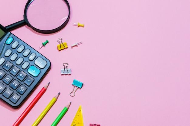 Varie forniture per ufficio su uno sfondo rosa torna al concetto di scuola vista dall'alto calcolatrice e p...