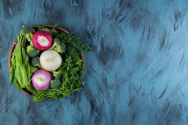 Vari ravanelli organici e foglie verdi su sfondo blu.