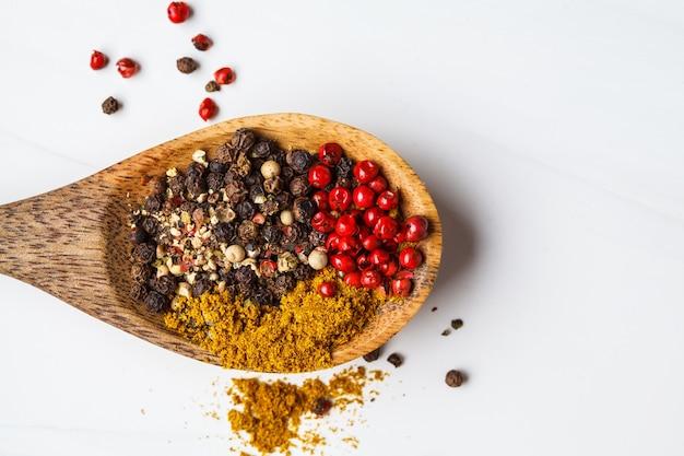 Vari peperoni e spezie su un cucchiaio di legno