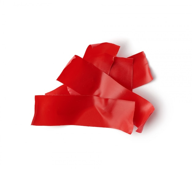 Vari pezzi di nastro isolante di gomma rosso isolato su uno sfondo bianco