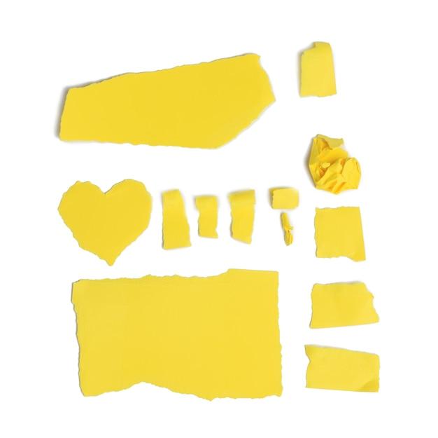 Vari pezzi di cartone giallo strappato isolati