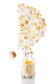 Varie pillole volano fuori da un barattolo di vetro a forma di lettera d, isolato su superficie bianca