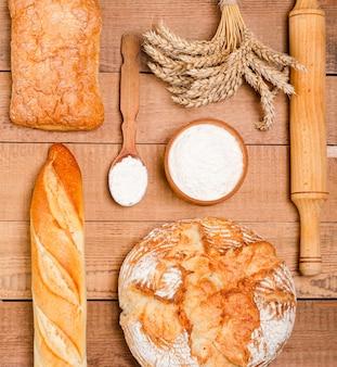 Varie pagnotte croccanti rustiche di pane e focacce su assi di legno.