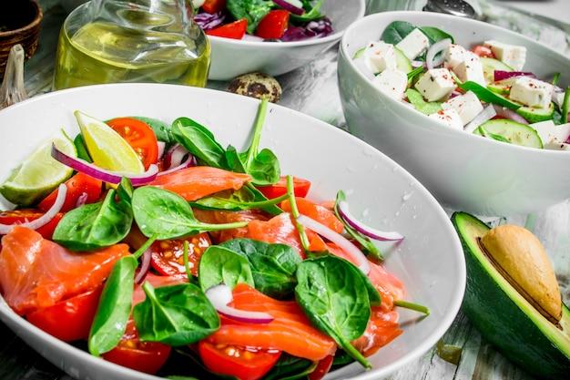 Varie insalate di verdure biologiche, pesce e formaggio con olio d'oliva e spezie. su fondo rustico.