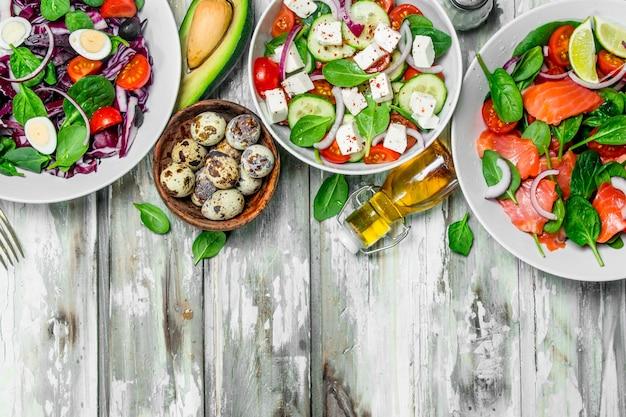 Varie insalate di verdure biologiche, pesce e formaggio con olio d'oliva e spezie sul tavolo rustico.