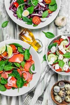 Varie insalate di verdure biologiche, pesce e formaggio con olio d'oliva e spezie.