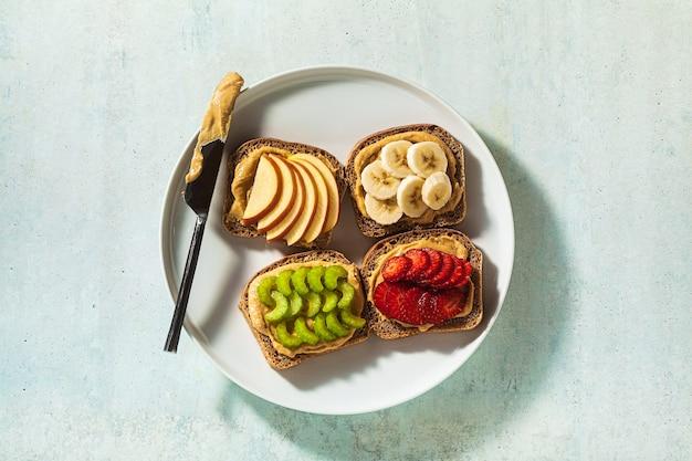 Vari panini con burro di arachidi e fragole, sedano, banana e mela su un piatto sul tavolo. perfetta colazione mattutina