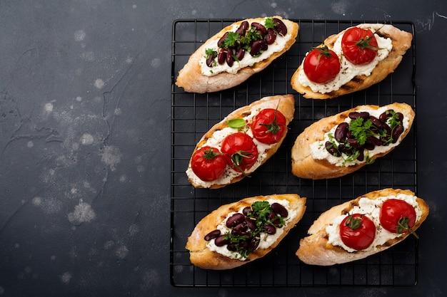 Vari panini con fagioli rossi, pomodorini al forno, aglio, olio d'oliva e ricotta su superficie scura