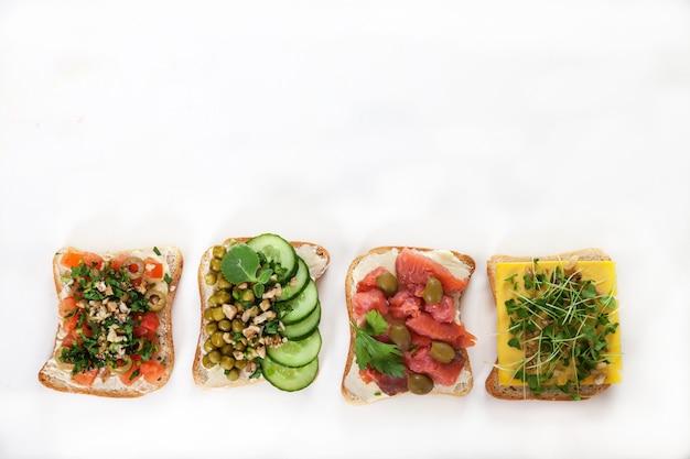 Vari panini con salmone salato, cetrioli, pomodori, piselli, olive, germogli su un piatto bianco.
