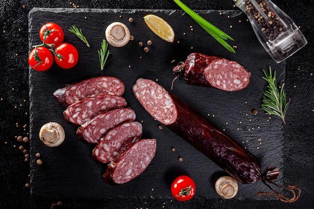 Varie salsicce e prodotti affumicati giacciono su un bordo nero, salsicce, salsicce, costolette, involtini