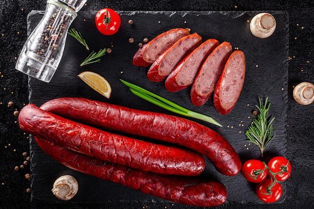 Varie salsicce e prodotti affumicati giacciono su un bordo nero