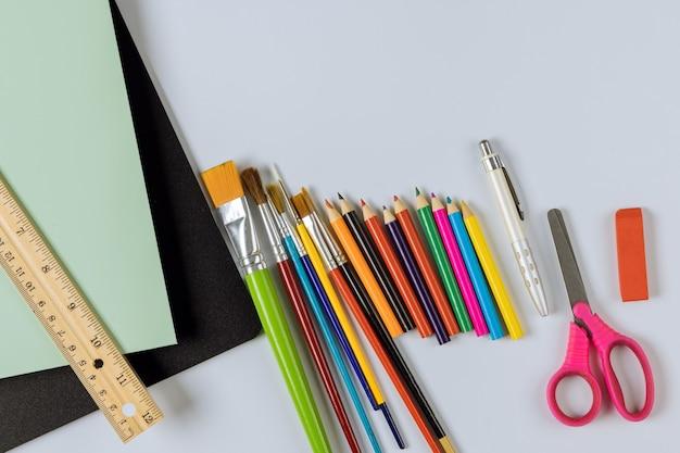 Varie forniture d'arte scolastiche sulla disposizione del gruppo di materiale studentesco nella tabella di disposizione piatta
