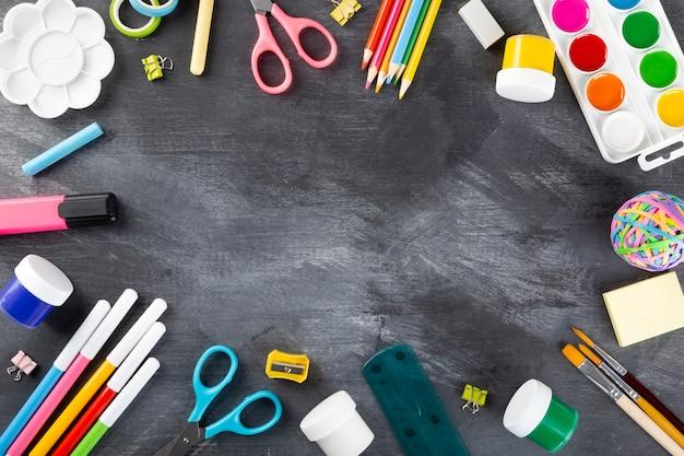 Vari ufficio scolastico e forniture di pittura su sfondo nero. torna al concetto di scuola. vista dall'alto. copia spazio