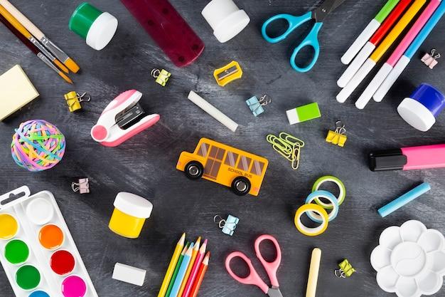 Varie forniture per ufficio scolastico e pittura su nero, piatto