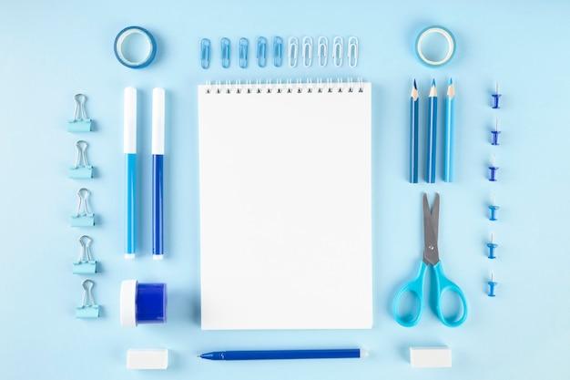 Varie forniture scolastiche e pittura su sfondo blu. torna al concetto di scuola. composizione geometrica e monocromatica. vista dall'alto. copia spazio