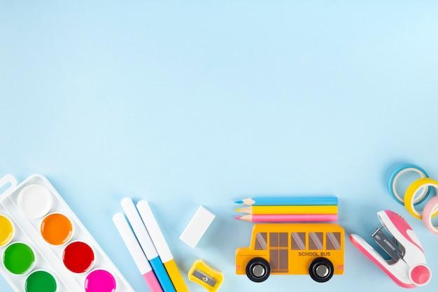 Varie forniture scolastiche e pittura su sfondo blu. torna al concetto di scuola. vista dall'alto. copia spazio