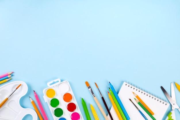 Vari rifornimenti dell'ufficio e della pittura di scuola su fondo blu. torna al concetto di scuola.