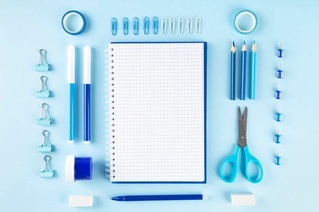 Varie forniture per ufficio scolastico e pittura su blu, piatto laici