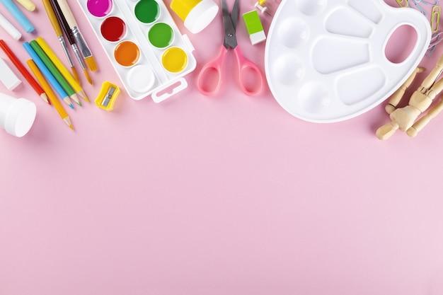 Varie forniture scolastiche e pittura su sfondo rosa. torna al concetto di scuola. vista dall'alto. copia spazio